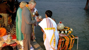The Prince of Wales and Duchess of Cornwall are given water to pour into the river Ganges.