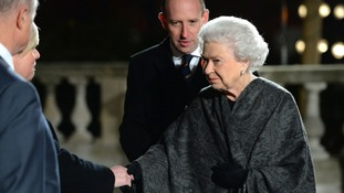 Queen Elizabeth II shakes hands with members of staff at the Royal Albert Hall.