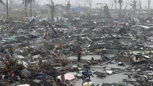 Survivors stand among debris and ruins of houses destroyed after Super Typhoon Haiyan battered Tacloban city in central Philippines.