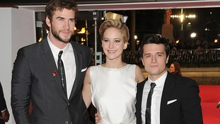 Jennifer Lawrence, Josh Hutcherson and Liam Hemsworth pose for media at the Hunger Games sequel premiere.