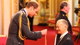 Sir Tony Robinson is knighted by the Duke of Cambridge during an investiture ceremony.