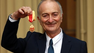 Sir Tony Robinson holds his medal after being knighted by the Duke of Cambridge at Buckingham Palace.