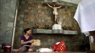 A woman puts a child to sleep behind the altar