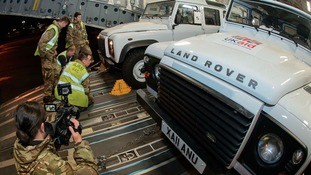 Land Rovers are loaded up to be taken to the Philippines to help with the relief effort