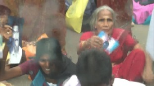 Women holding pictures of their missing relatives stage a sit-down protest in Jaffna, Sri Lanka.