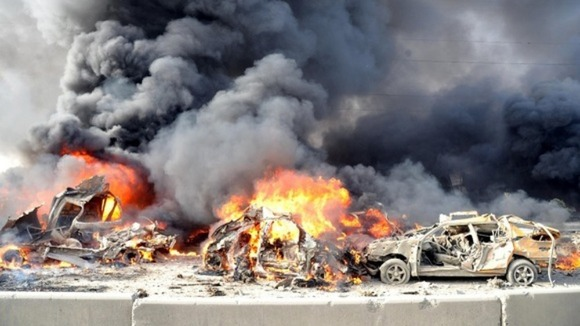 Flames and smoke rise from burning cars after two bombs exploded in Syria.