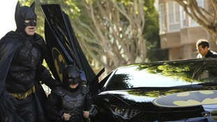 Miles hops out of Batman's famous Batmobile car.