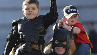 Miles waves to the crowd on the shoulders of Batman.