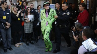 The Riddler is taken away by a San Francisco Police officer after being apprehended by the five-year-old.