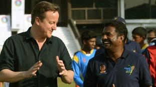 David Cameron chats to the former Sri Lankan cricketer Muttiah Muralitharan at Colombo's National Cricket Academy