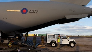 RAF ground crew unload emergency supplies of JCB diggers and Land Rovers from a C-17 transporter plane at Cebu airport in the Philippines
