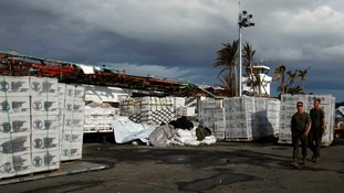 US servicemen walk past relief goods at Tacloban airport in the Philippines.