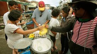 A woman sells salt and eggs along a main street in the Typhoon Haiyan devastated town of Palo, near Tacloban.