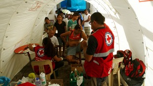Residents receive medical aid from the Philippine Red Cross outside their temporary shelters in Tacloban.