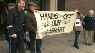 Campaigners waving home-made banners at Barnsley library