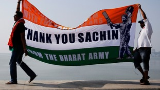 Cricket fans walk on a sea wall while holding a banner thanking cricketer Sachin Tendulkar.
