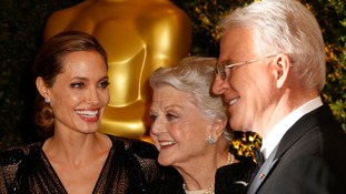 Angelina Jolie, Angela Lansbury and Steve Martin laugh on the red carpet.