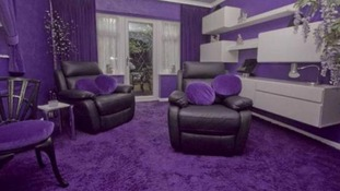 The living room boast purple walls, carpets and cushions.