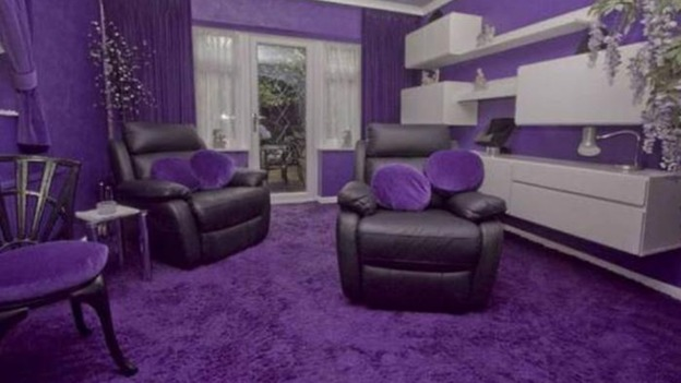 The Living Room Boast Purple Walls Carpets And Cushions