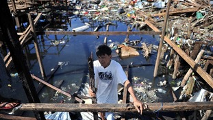 A Filipino man is seen amongst the ruins of typhoon-ravaged Tacloban city in the Philippines.