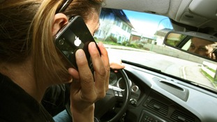 A driver uses a phone while behind the whee. Reconstruction.