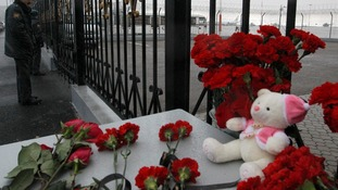 Flowers and a teddy bear are left near a fence of Kazan airport, where the plane crashed on Sunday.