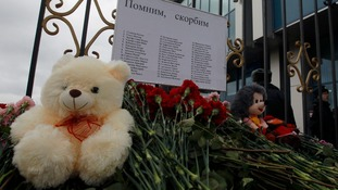 Flowers and stuffed toys, part of a makeshift memorial, are seen left near a fence of Kazan airport.