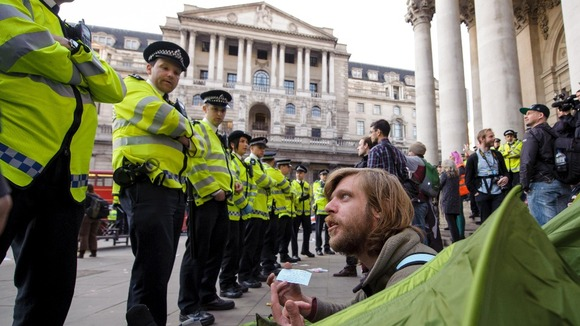 An Occupy demonstrator inside a tent speaks with police officers