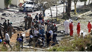 Lebanese army soldiers, members of the Red Cross and forensic inspectors examine the site of explosions