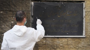 A forensic inspector collects evidence from the burnt plaque of the Iranian embassy in Beirut
