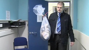 Detective Inspector Steve Hull, from Lincolnshire Police, carries the money in for investigation.