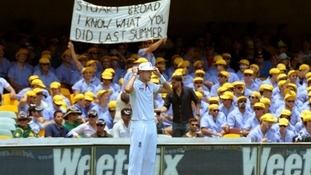 Australian supporters hold a banner as England's Stuart Broad fields on the boundary at The Gabba in Brisbane.