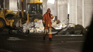 An emergency service personnel walks past rubble from the collapsed Maxima supermarket in Riga, Latvia.