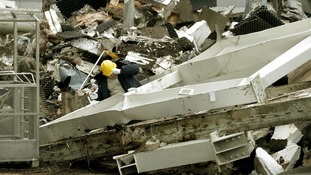An expert inspects construction elements from a collapsed supermarket in Latvian capital Riga