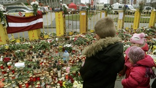 Children gather to pay their respects at the site of the Latvia supermarket collapse.