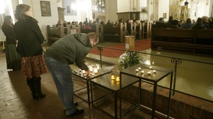 People attend a mass in the Doma church for the victims of the collapsed supermarket.
