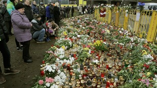 People gather near the collapsed supermarket in Riga to pay their respects today.