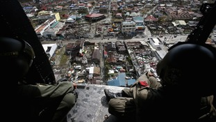 Members of the Philippine Air Force survey the damage in Tacloban from the air