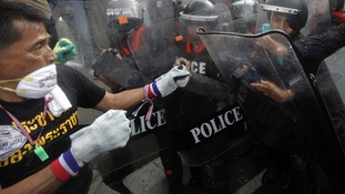 A protester challenges police during an anti-government rally in Bangkok today