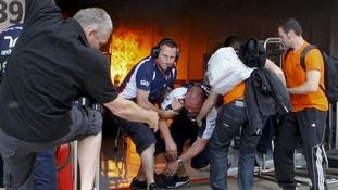Team members are dragged from the Williams garage after a blaze broke out