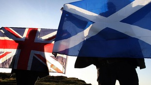 Two men hold up a Scottish flag and a Union flag.