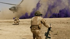 British soldiers cover themselves from dust as a helicopter lands in Helmand