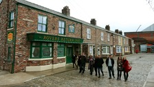 Cast members from Coronation Street walk along the cobbles of the new set.