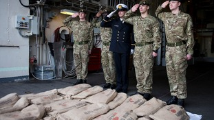 Members of the UK and Belgium military salute in front of the sacred soil aboard the Belgian Frigate Louise Marie.