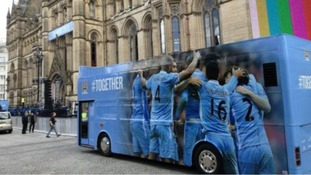 An open top bus arrives at Albert Square ahead of Manchester City's parade through the city.