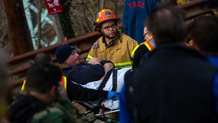 Man taken away on stretcher at site of Metro-North train derailment.