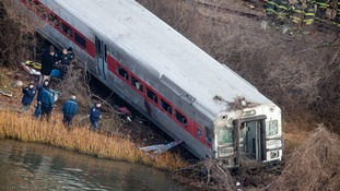 Emergency workers examine the site of a Metro-North train in New York City.