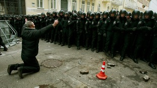 A man kneels down while riot police stand guard near the presidential administration