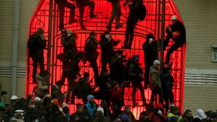 People climb up onto a gate near the presidential administration building in Kiev