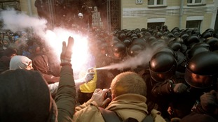 Protesters try to break through police lines near the presidential administration building